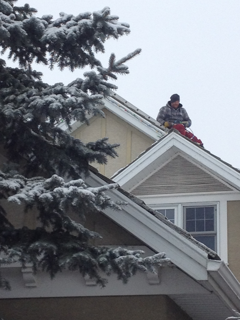 person hanging christmas lights on roof above second story - How To Put Christmas Lights On Roof